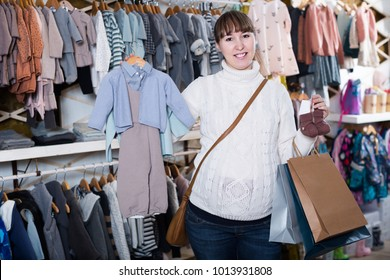 Happy pregnant mother choosing clothes for baby in children`s cloths shop