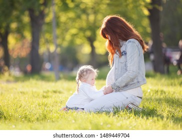 Happy pregnant mother and daughter in the autumn park. Beauty nature scene with family outdoor lifestyle. Happy woman and girl resting together on green grass, having fun outdoor
