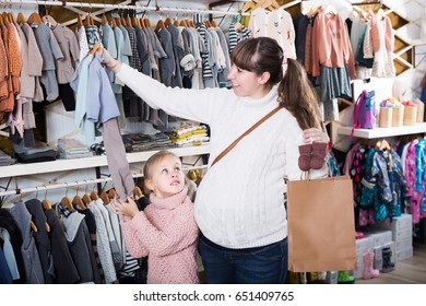 Happy pregnant mother and daughter choosing clothes for baby in childrenâ??s cloths shop. Focus on girl