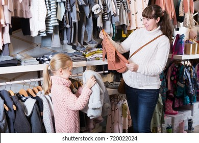 Happy pregnant mother and daughter examining clothes for baby in children`s cloths shop