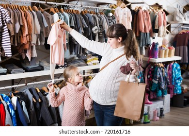 Happy pregnant mother and daughter examining romper suits for baby in children`s cloths store