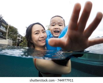 Happy pregnant mother and her son swimming in the pool.