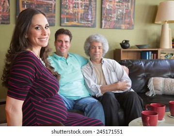 Happy pregnant surrogate female with mixed gay couple