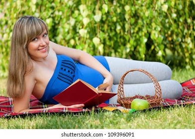 Happy pregnant woman with book in park outdoors