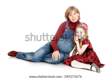 3705eb79f9cf9 Happy pregnant woman in denim overalls in the arms of his little daughter -  Isolated on