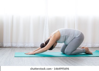 Happy pregnant woman doing yoga at home. Healthy pregnancy, sport, fitness, people and healthy lifestyle concept.