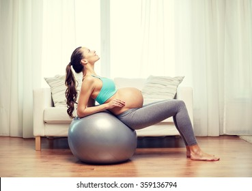 happy pregnant woman exercising on fitball at home