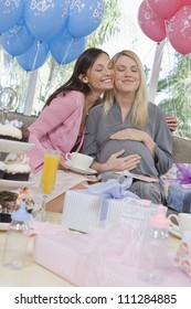 Happy pregnant woman with friend at a baby shower