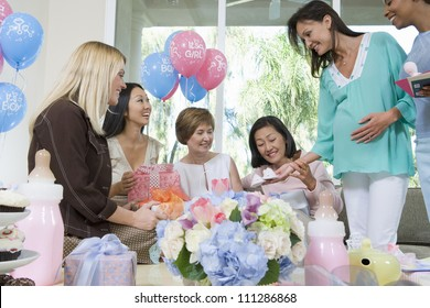 Happy pregnant woman and friends with presents at a baby shower