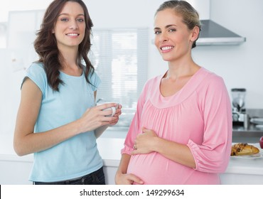 Happy pregnant woman and her friend posing in the kitchen