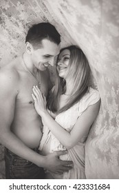 happy pregnant woman and her husband embracing at home