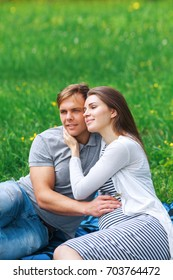happy pregnant woman with her husband hugging and smiling in park in summer