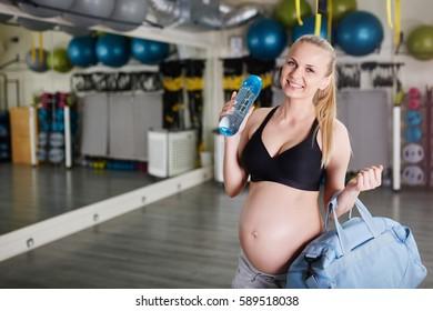 Happy pregnant woman holding bag and bidon at gym
