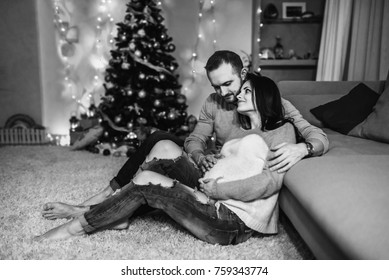 Happy pregnant woman with husband at home with christmas decorations