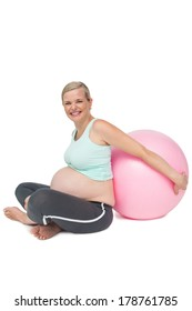 Happy pregnant woman leaning against pink exercise ball on white background