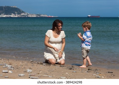 Happy pregnant woman playing with child boy and enjoying sunny day on the beach in Spain.
