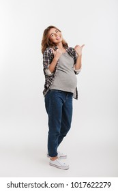 happy pregnant woman showing thumbs up isolated on grey