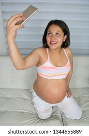 Happy pregnant woman taking selfie while sitting on bed.
