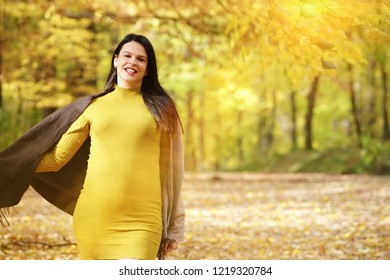 Happy pregnant woman walking through fall, autumn park. Copy space