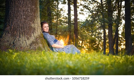 Happy pregnant young woman sitting leaning against a huge tree