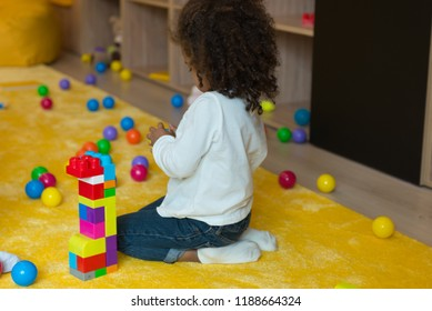 Happy preschool age children play with colorful plastic toy blocks. Creative kindergarten kids build a block tower. Educational toys for toddler or baby.