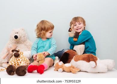 Happy preschool age children play with plush toys