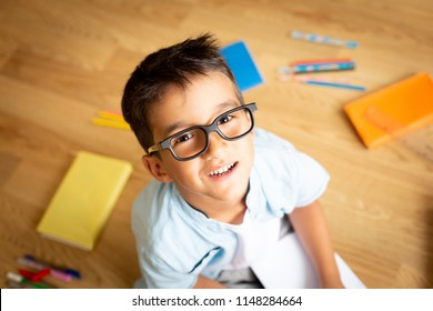 Happy preschool boy with eye glasses smiling, sitting on the floor with colorful books and pens, looking to the camera, home schooling and back to school concept