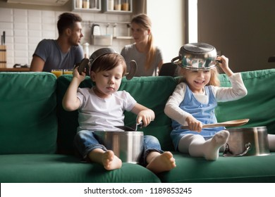 Happy preschool girl and boy playing with kitchenware on sofa at home, little sister and brother laughing using pots as drums and hats, holding kitchen utensils, making noises, spending time together