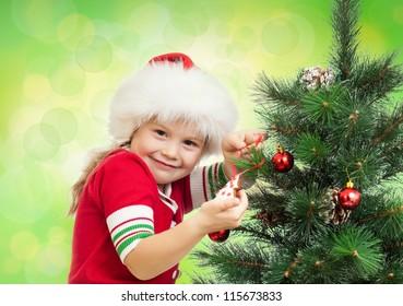 happy preschool girl decorating Christmas tree on green background