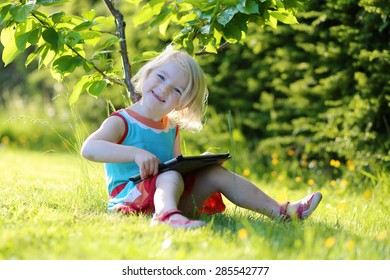 Happy preschooler child playing with tablet pc sitting in the garden on the grass. Cute little girl relaxing outdoors in the park enjoying sunny summer day. Young generation leisure.