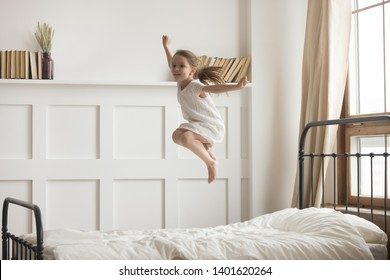 Happy preschooler girl have fun jumping high on comfortable mattress on bed at home, excited little child entertain enjoy playing alone leap and hop in white bedroom engaged in funny activity