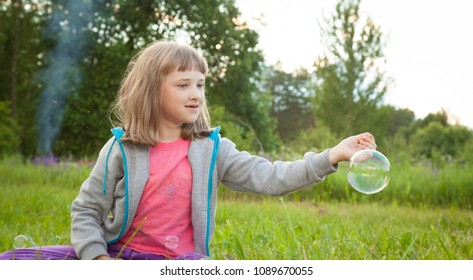 Happy preschooler girl playing with soap bubbles sitting in a summer park