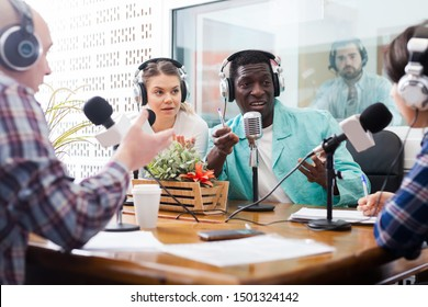 Happy presenters of different nationalities in sound broadcasting station hosting live radio show
