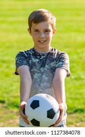 Happy pre-teen boy holding a football in a park