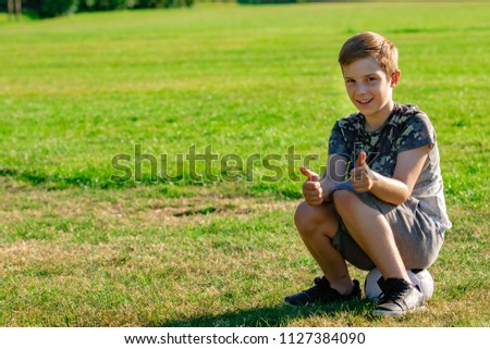 Happy pre-teen boy sitting on a football. Won a match concept