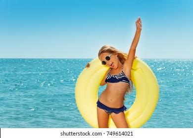 Happy preteen girl enjoying summer by the seaside