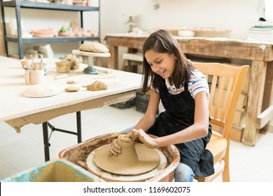 Happy preteen girl pursuing hobby of pottery while sitting in class