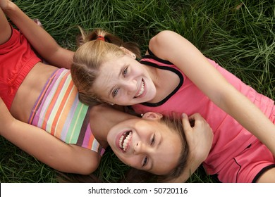 Happy preteen girls lying and playing on green grass