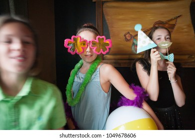 Happy Preteen Kids Having Fun with Photo Booth Props at a Party .