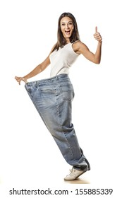 happy pretty attractive girl posing in huge pants with the thumbs up
