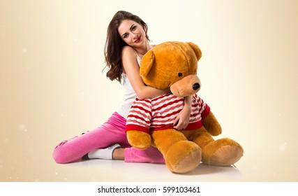 Happy pretty brunette girl with pajamas on ocher background