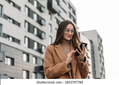Happy pretty brunette girl using mobile phone near office, beautiful woman browsing phone and doing online shopping in a mobile app while smiling walking near shopping mall.