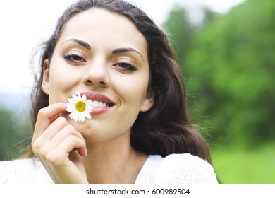 Happy pretty brunette woman in field, cute female relaxed on flowers meadow, spring nature, having fun outdoor