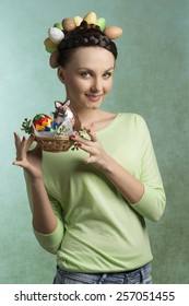 Happy, pretty brunette woman with funny hairstyle with eggs and easter basket filled by decorations. She wears green blouse.