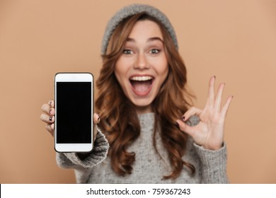 Happy pretty brunette woman showing blank mobile screen and OK gesture, selective focus on screen
