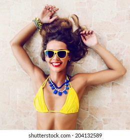 Happy pretty brunette woman smiling and having fun in hot summer day, wearing stylish neon bikini sunglasses and jewelry.