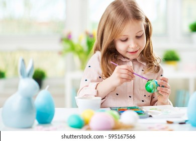 Happy pretty child girl having fun during painting eggs for Easter in spring time at home