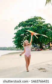 Happy pretty child girl with a kite running on tropical beach in summer. Sea fun, childhood concept
