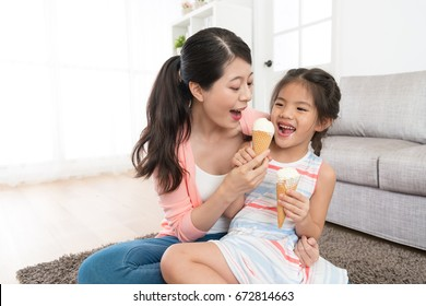 happy pretty daughter children playing with mother in living room and grabbing mom's ice cream want to eating enjoying summer season.