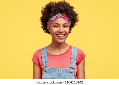 Happy pretty female housewife dressed in casual t shirt and denim overalls, has broad smile as did all work about house, poses against yellow background indoor. African American woman giggles
